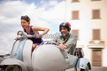 couple driving a scooter
