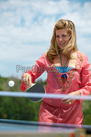 older woman playing table tennis outside