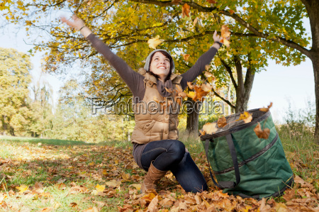 woman playing with fall leaves in