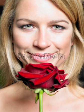 young woman holding red rose smiling