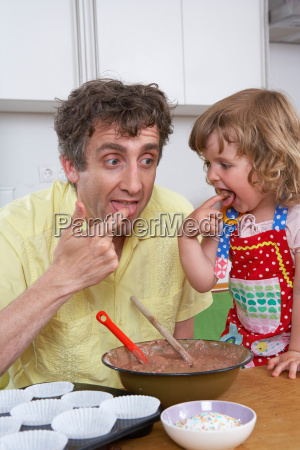 father and daughter tasting batter