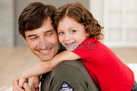 daughter riding on fathers back