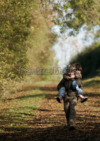 boy carrying young child in countryside