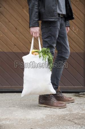 nastoletni chlopiec niosacy torby na zakupy