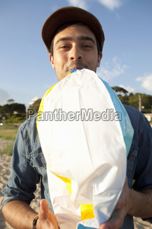 young man blowing up beach ball