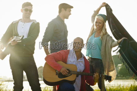 four adult friends with acoustic guitar