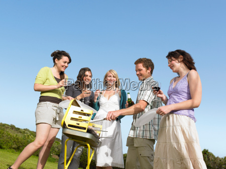 group of young people by barbecue