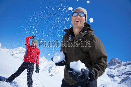 young couple playing in snow