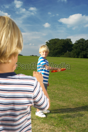 boy throwing frisbee to another boy
