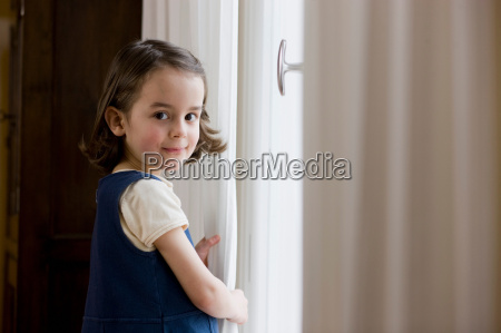 young girl standing at curtains
