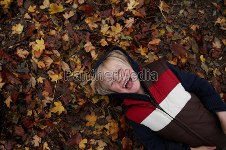 young boy lying on autumn leaves