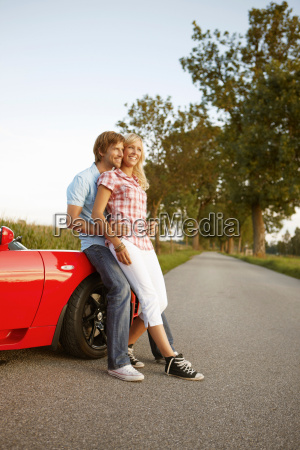 couple sitting on electric sports car