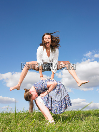 young women playing leapfrog