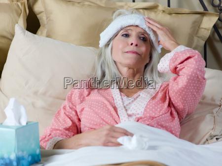 chora starsza kobieta lezaca w lozku