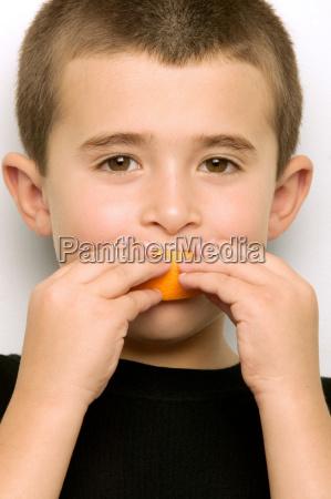 chlopiec jedzenia pomaranczowy segmentu