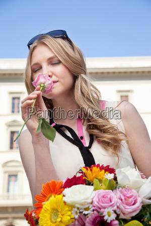 mloda kobieta pachnace wzrosla z bukietem
