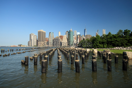 wooden posts in river cityscape behind