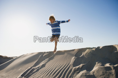 boy jumping on sand dune