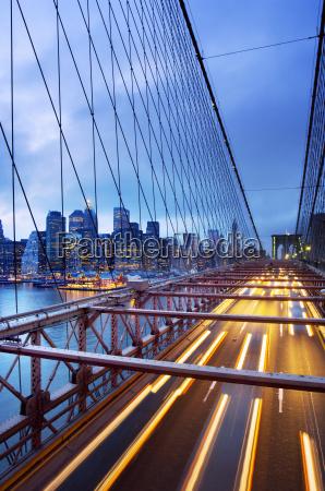 brooklyn bridge with traffic at dusk