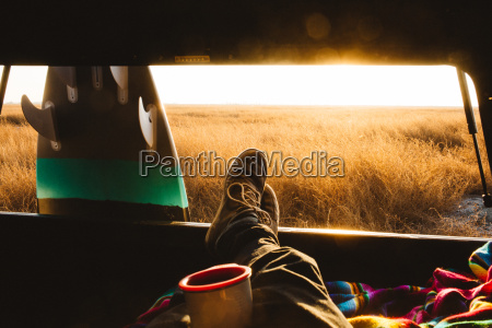 male surfer with feet up in