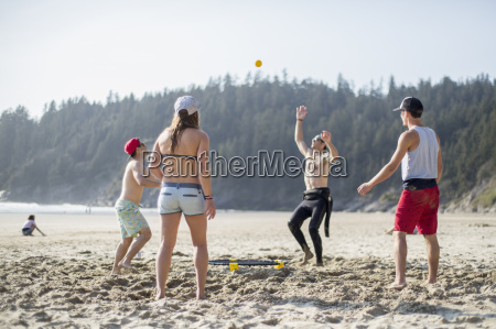 four adult friends throwing and catching