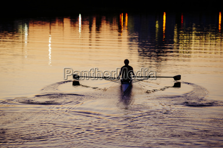 young man rowing on river at