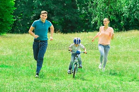 rodzice biegaja z synem jadacym na
