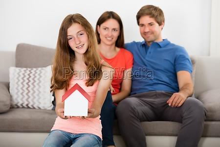 girl holding small house model