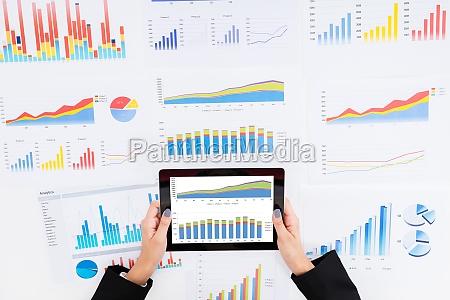businesswoman analyzing financial graphs using digital