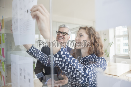 businessman and woman looking at paper
