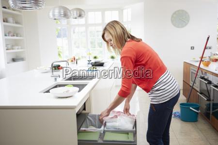 kobieta stojacy w kuchni oprozniania pojemnika