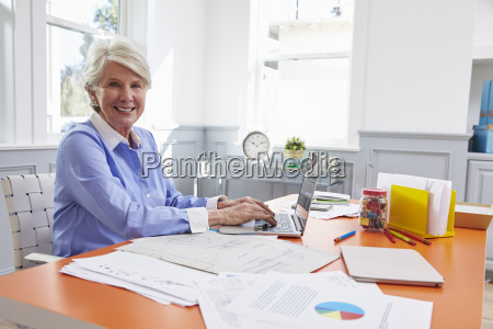 senior kobieta siedzi na biurku i