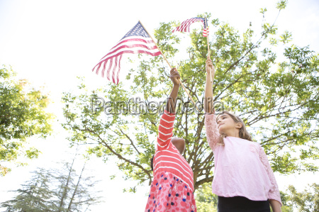 girls holding up american flags in