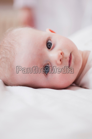 baby lying in bed looking at