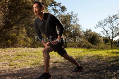 runner stretching in park