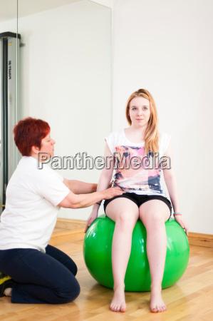 mloda kobieta siedzi na kuli fitness