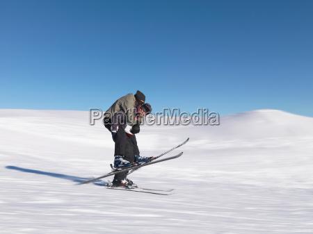 skier giving friend piggyback ride