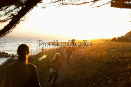 family walking by coast at sunset