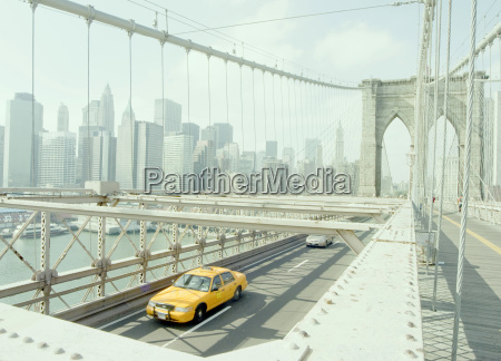 yellow taxi crossing brooklyn bridge new