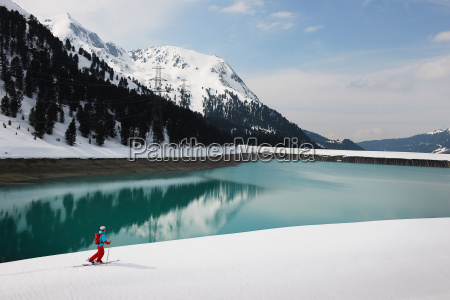 solitary skier by lake and mountain