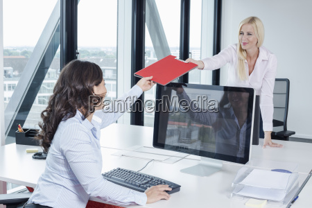 woman giving colleague file in office