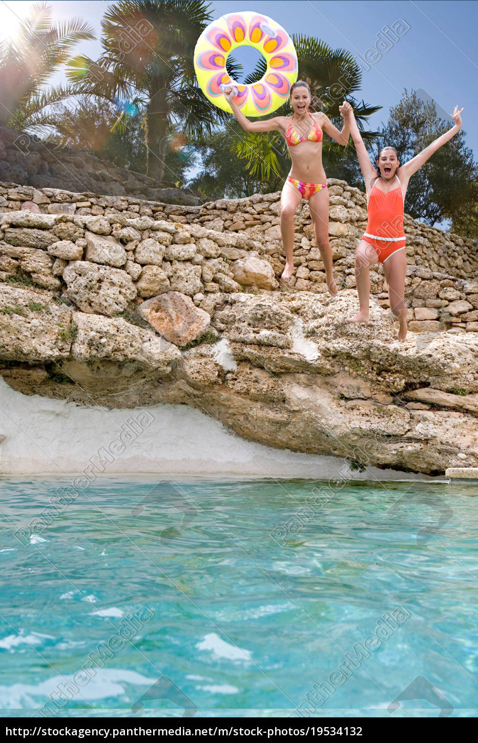 young, women, jumping, into, stone, pool - 19534132