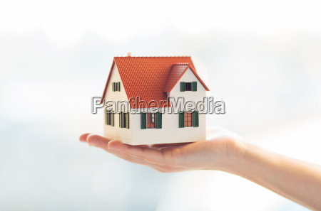 close up of hands holding house