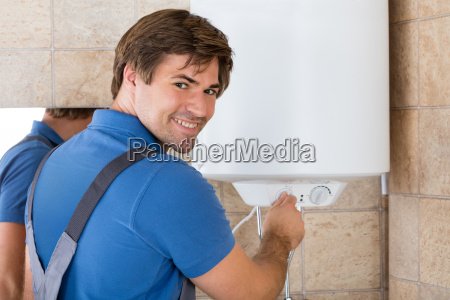 happy, young, repairman, holding, knob, of - 20118929