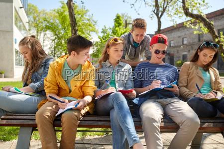 grupa studentow z notatnikami na podworku