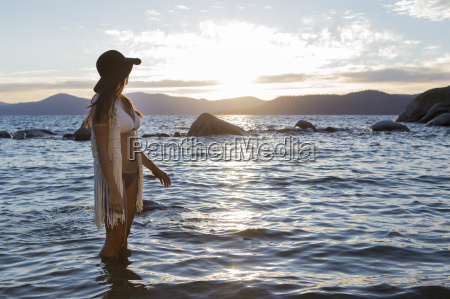 woman standing in water during sunset
