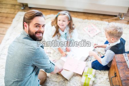 ojciec i dzieci pakowanie prezentow