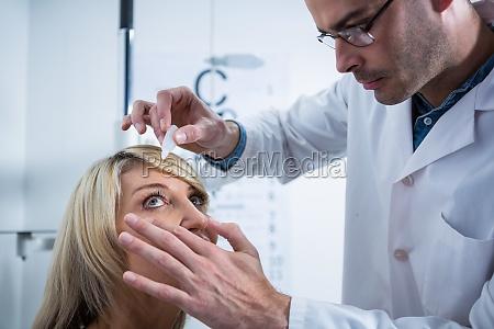 okulista wprowadzenie krople do oczu pacjentow