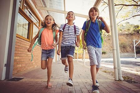 szczesliwe dzieci szkolne dzialajace w korytarzu