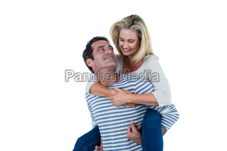 romantic man carrying woman piggyback